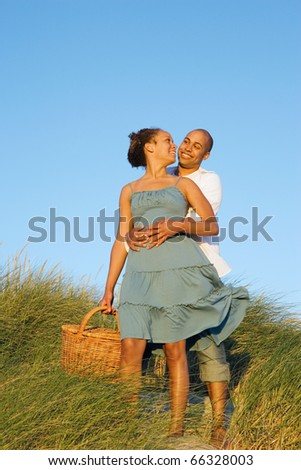 Couple hugging with picnic basket at beach - stock photo