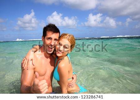 Couple in a caribbean lagoon showing thumbs up - stock photo