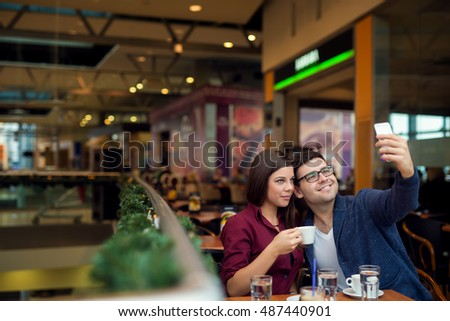 Couple in a coffee shop, taking a picture of themselves.