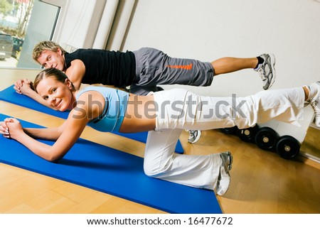 Couple in a gym performing gymnastics that are supposed to make a sexy ass. Judging from the models it might work.