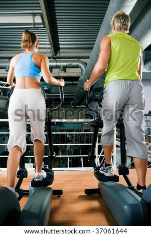 Couple in a gym working out on a cross trainer