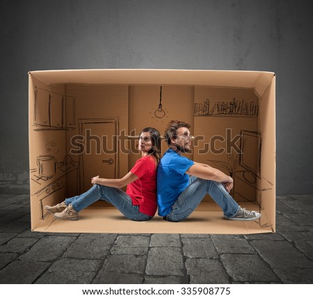 Couple in a house designed in cardboard - stock photo