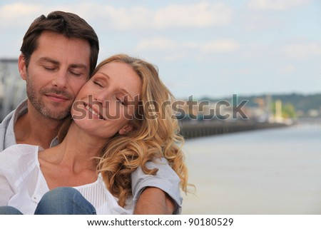 Couple in a loving embrace on the waterfront of Bordeaux - stock photo