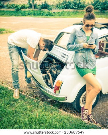 Couple in a moment of troubles during a vintage classic car trip - Concept of modern relationship and interaction with new technologies - Problem solving and lifestyle - stock photo