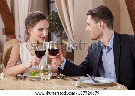 Couple in a restaurant drinking red vine - stock photo