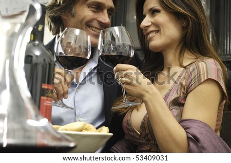 Couple in a restaurant drinking wine - stock photo