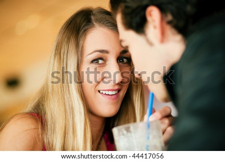 Couple in a restaurant or diner, drinking a milkshake using a straw, shot with available light, very selective focus
