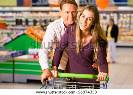 Couple in a supermarket shopping equipped with a shopping cart buying groceries and other stuff, they are are both having fun with the store and each other - stock photo