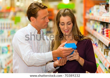 Couple in a supermarket shopping groceries and other stuff, they are looking for what they need - stock photo