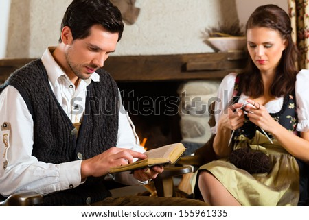 Couple in a traditional mountain hut with fireplace knitting and reading the bible