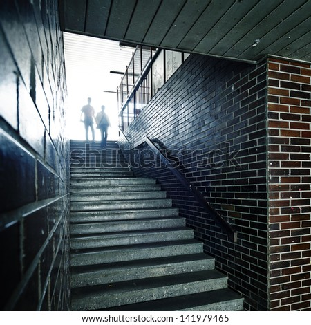Couple in a void passage with dirty stairway - stock photo