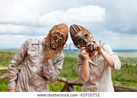 Couple in African masks standing at balcony with view to savanna