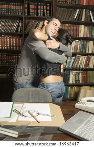 Couple in an office hugging - stock photo