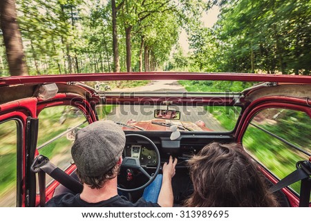 Couple in an ondtimer convertible, driving through the woods, carefree, enjoying the ride - stock photo