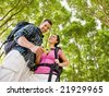 Couple in backpacks looking at compass - stock photo