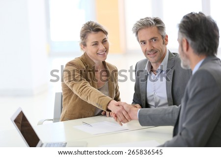 Couple in bank office shaking hand to financial adviser - stock photo