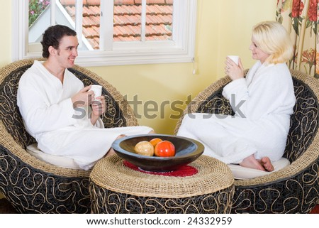 couple in bathrobe chatting in the bedroom - stock photo