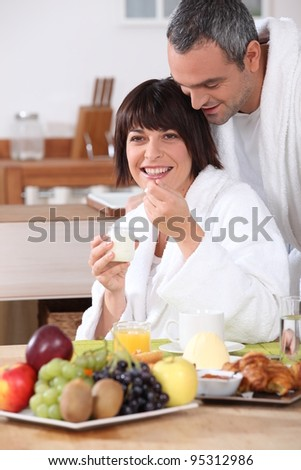 Couple in bathrobe having breakfast - stock photo