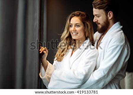 Couple in bathrobes enjoying honeymoon in spa resort - stock photo