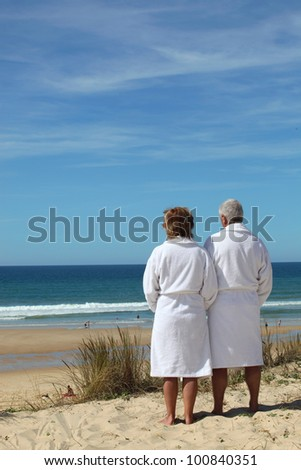Couple in bathrobes watching the sea - stock photo