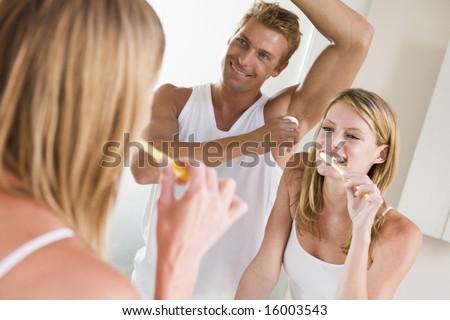 Couple in bathroom brushing teeth and applying deodorant - stock photo