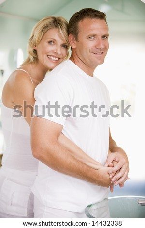 Couple in bathroom embracing and smiling - stock photo