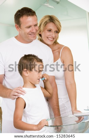 Couple in bathroom with young boy brushing teeth - stock photo