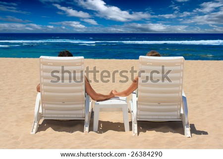 Couple in beach chairs holding hands near ocean - stock photo