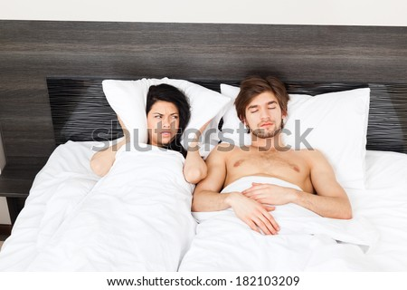 Couple in bed, snoring man. woman can not sleep, covering ears with pillow for snore noise, sleeping in bedroom at home - stock photo