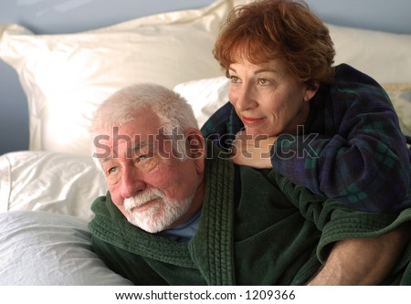 Couple in bedroom watching sunrise - stock photo