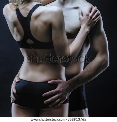Couple in black lingerie. Seductive couple on the dark background. - stock photo
