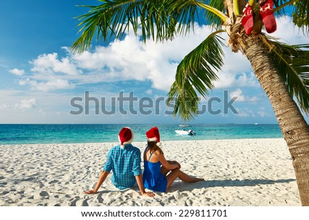 Couple in blue clothes on a tropical beach at christmas - stock photo