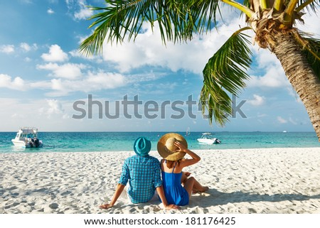 Couple in blue clothes on a tropical beach at Maldives - stock photo