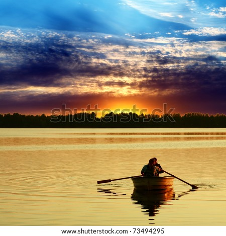 Couple in boat against a beautiful sunset - stock photo
