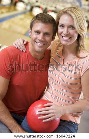 Couple in bowling alley holding ball and smiling - stock photo