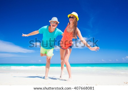 couple in bright clothes having fun at tropical beach - stock photo