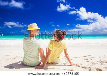 Couple in bright clothes having fun at tropical beach