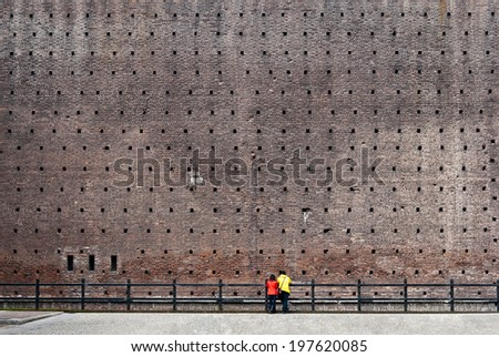 Couple in bright clothing standing in front of high brick wall - stock photo