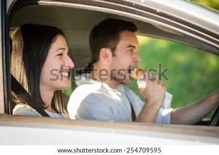 Couple in car - man driving and eating - stock photo