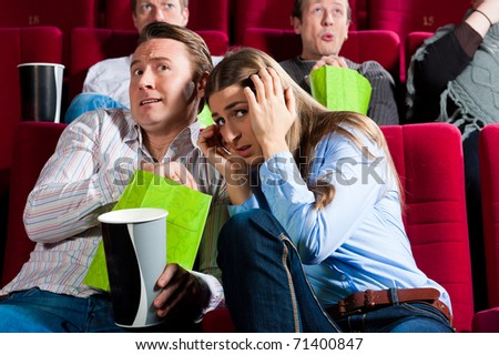 Couple in cinema watching a movie; it seems to be a horror movie - stock photo