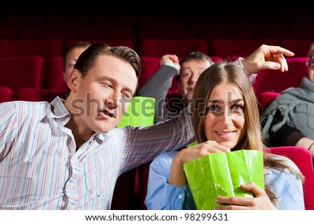 Couple in cinema watching a movie, they eating popcorn - stock photo