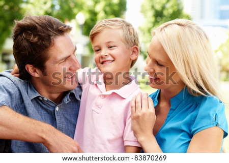 Couple in city park with young son - stock photo