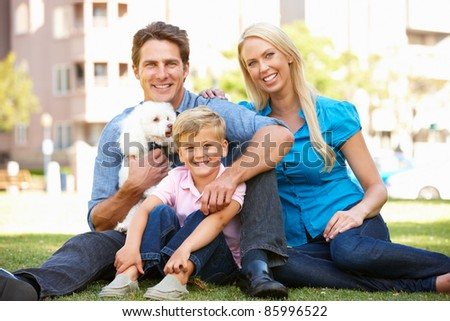 Couple in city park with young son and dog - stock photo