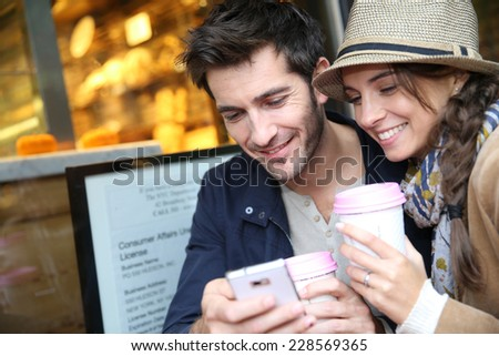 Couple in coffee shop connected with smartphone - stock photo