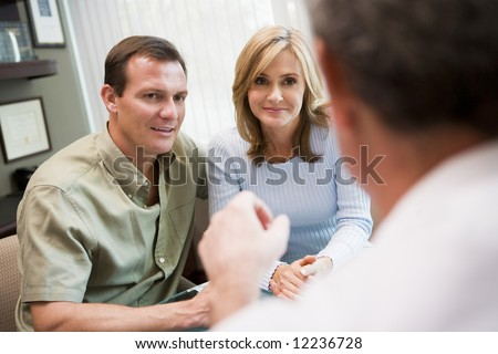 Couple in consultation at IVF clinic talking to doctor - stock photo