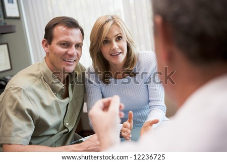 Couple in consultation at IVF clinic talking to physician - stock photo