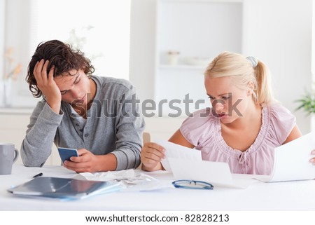 Couple in despair while doing accounts in the living room