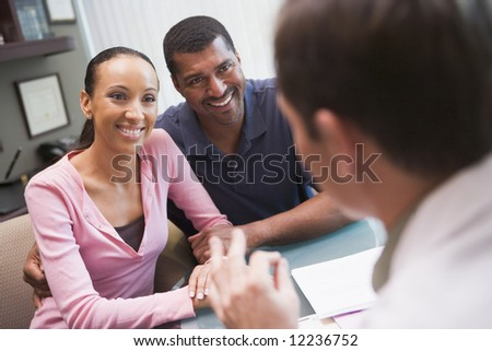 Couple in discussion with doctor in IVF clinic sitting at desk - stock photo