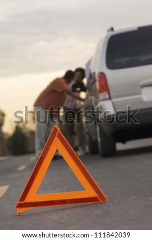 Couple in discussion with warning triangle in foreground