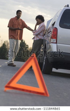Couple in discussion with warning triangle in foreground - stock photo